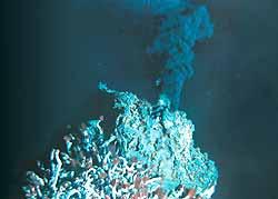 Темная горячая и богатая минералами вода выбрасывается из черного курильщика